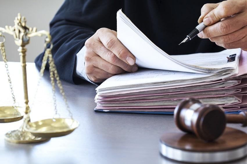 professionnel tenant un stylo au-dessus d'un classeur avec documents