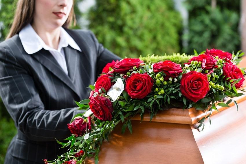 femme se tenant à côté d'un cercueil sur lequel est posé un coussin de fleurs de deuil avec des roses rouges